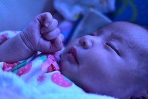 いちご柄の服を着て眠る赤ちゃん(ホワイトバランス調整)