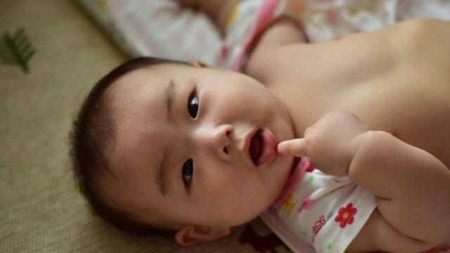 口元に指を当てて笑っている赤ちゃん