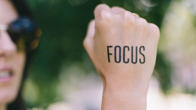 focusと書かれた手を掲げる女性