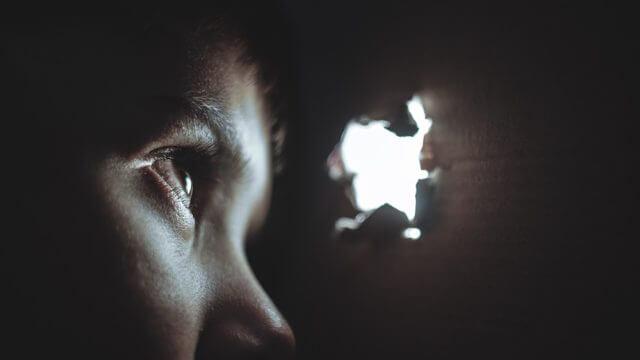暗がりでのぞき穴を覗く人