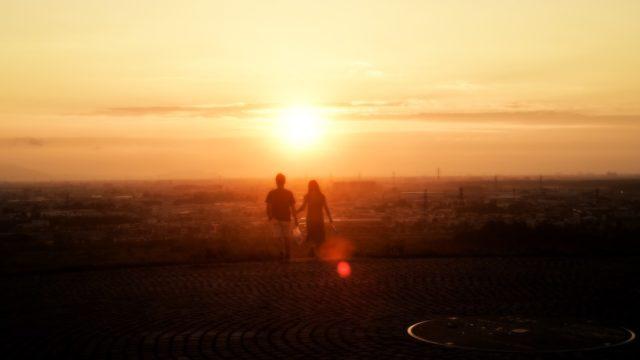 夕日の前に手をつないで歩く二人