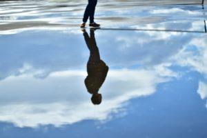 水たまりの前に佇む女性